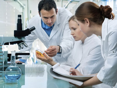 Three people in lab coats looking at a pitri dish next to a microscope