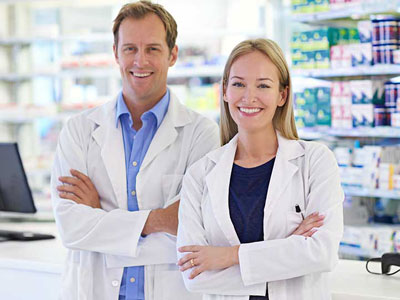 Male and Female pharmacists in lab coats standing next to each other and smiling