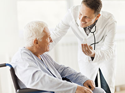 Long-Term Care Facilities: A doctor speaking with an elderly man in a wheelchair
